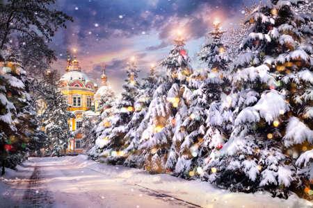 espiritu santo: Iglesia con �rboles de Navidad iluminados en las nevadas en la v�spera de Navidad en invierno