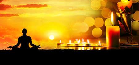 Kaarsen op de achtergrond bokeh en man doet meditatie bij zonsondergang.