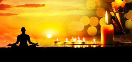 meditate: Lighting candles at bokeh background and man doing meditation at sunset.