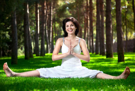 meditative: Yoga by happy woman in white costume on green grass in the park around pine trees
