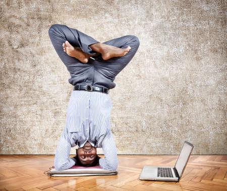 cabeza abajo: Hombre de negocios indio haciendo parada de cabeza pose de yoga y mirando a su computadora portátil en la oficina al fondo de textura marrón