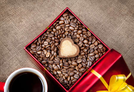 valentine day cup of coffee: Coffee grains with heart shape cookie in Red box with yellow ribbon and mug with black coffee on textured brown background on Valentines day Stock Photo