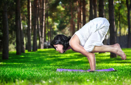 Yoga bakasana crane pose by woman in white costume on green grass in the park around pine trees
