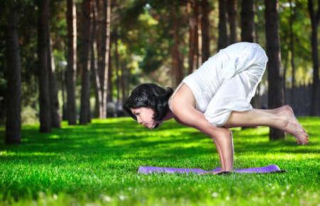 corvini: Yoga Bakasana gru posa da donna in costume bianco su erba verde nel parco intorno agli alberi di pino