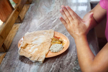 Woman praying in front of masala dosa Indian traditional vegetarian dish with coconut chutney in India photo