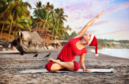 Goa: Yoga by young woman in red costume and red christmas hat on the beach near the ocean at tropic background in India