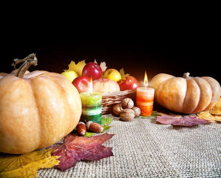 Thanksgiving day pumpkins, apples in the basket, acorns, walnuts, candles with light and autumn leaves around on textured cloth at black background. Free space for your text photo