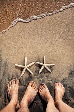 Legs of young couple standing on the beach near two starfishes on the sand with ocean near by photo