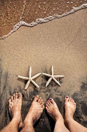 luna de miel: Piernas de joven pareja de pie en la playa cerca de dos estrellas de mar en la arena con vista al mar cerca de