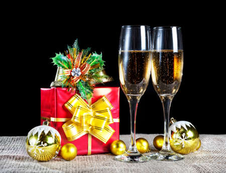 Christmas red box with yellow ribbon and two glasses with champagne at black background. Free space for your text photo