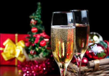 champers: Two glasses with champagne and red box with yellow ribbon, Christmas tree and Christmas balls in the basket at black background. Free space for your text