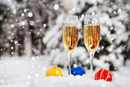 Two glasses with champagne and colorful Christmas balls on the snow in Christmas time
