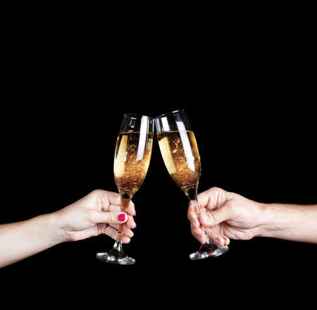 Couple holding two glasses with champagne at black background. Free space for your text