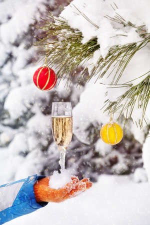 Hand in orange glove with glass of champagne and colorful Christmas balls on the tree in Christmas time photo
