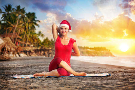 Christmas Yoga gomukhasana cows head pose by young woman in red costume and red christmas hat on the beach near the ocean at sunset background in India  photo