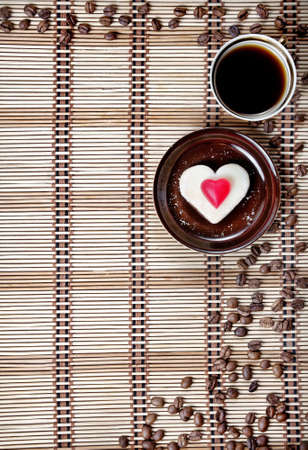 Cup of coffee and cookie with marmalade candy in shape of heart and coffee beans around photo