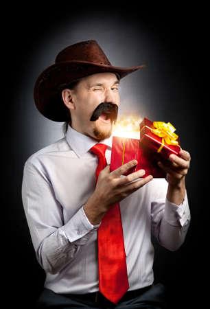 bigote: Vaquero con gran bigote y guiñando abrir la caja de regalo de color rojo con el interior de la luz que brilla intensamente en fondo negro