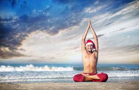 Christmas yoga by man in red trousers and Christmas hat on the beach near the ocean in India