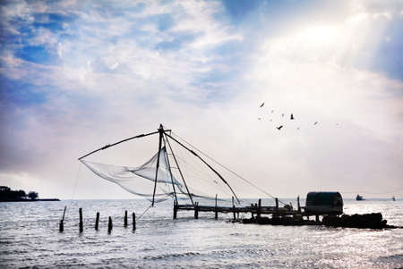 chinese fishing nets: Chinese Fishing nets at blue cloudy sky background on Vypeen Island in Kochi, Kerala, India