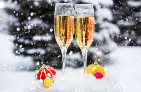 Two glasses with champagne and Christmas balls on the snow in Christmas time Stock Photo