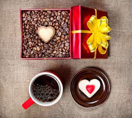 Coffee grains with heart shape cookie in Red box with yellow ribbon, mug with black coffee and source with candy on textured brown background on Valentines day photo