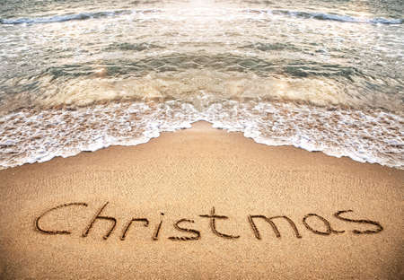 Christmas title on the sand beach near the ocean photo