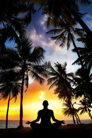 position: Yoga meditation silhouette by man at palms, ocean and sunset sky background in India