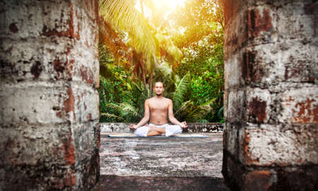 dhyana: Yoga meditation by man with beard in white trousers on the roof at palms and sunset sky background in India Stock Photo