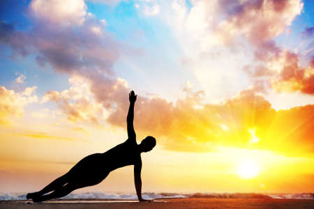 plank position: Yoga vasisthasana, side plank pose by woman in silhouette with sunset sky background. Free space for text