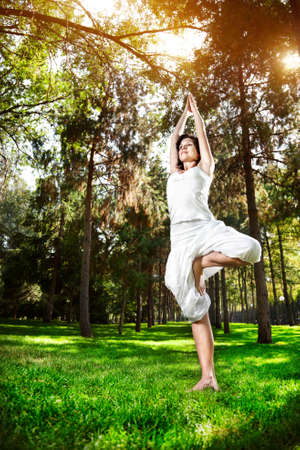 Yoga tree pose by woman in white costume on green grass in the park around pine trees photo