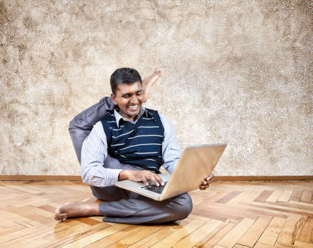shirshasana: Happy Indian businessman with leg behind his head typing on his laptop and smiling in the office at brown background Stock Photo