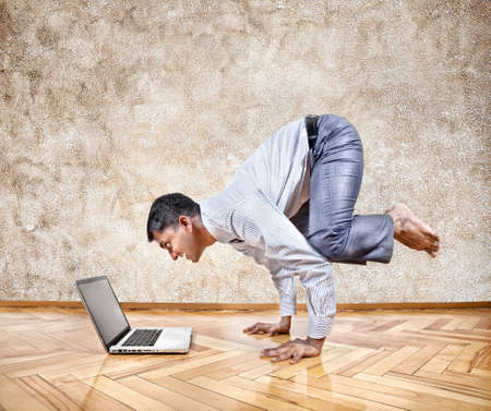 Indian businessman doing yoga hand stand pose and looking at his laptop in the office at brown textured background