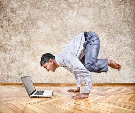 Indische zakenman doet yoga kant staan poseren en kijken naar zijn laptop in het kantoor op bruine geweven achtergrond