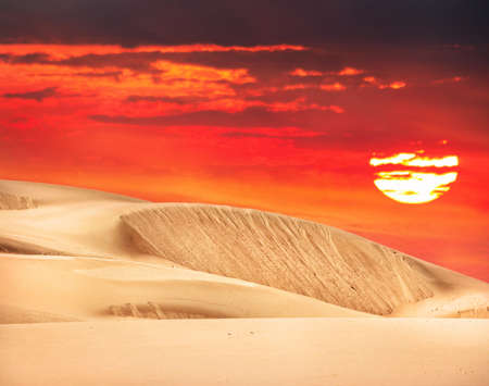 Desert with orange sky and big sun in Kazakhstan, Central Asia Stock Photo