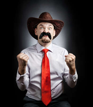 enrage: Angry Cowboy with big moustache showing his fists at black background Stock Photo