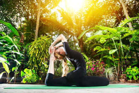 Yoga Raja Kapotasana pigeon pose by woman in black costume in the garden with palms, banana trees and plants in the pots photo