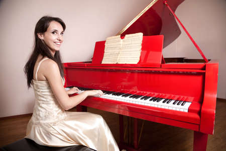 Happy woman in dress playing the red grand piano, smiling and looking at camera