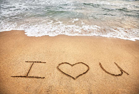 Handwriting expression of love on the sand beach near the ocean photo