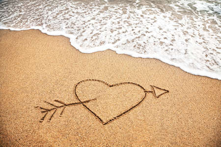 Handwriting Heart with arrow on the beach near the ocean photo