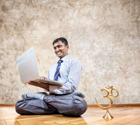 Happy Indian businessman doing yoga and typing on his laptop with om statue near by in the office at brown background photo