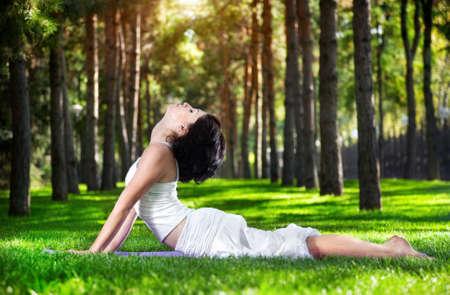 serpiente cobra: Yoga Bhujangasana actitud de la cobra por mujer en traje blanco sobre la hierba verde en el parque alrededor de los �rboles de pino