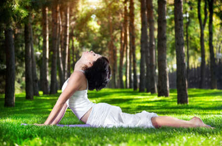 Yoga bhujangasana cobra pose by woman in white costume on green grass in the park around pine trees photo