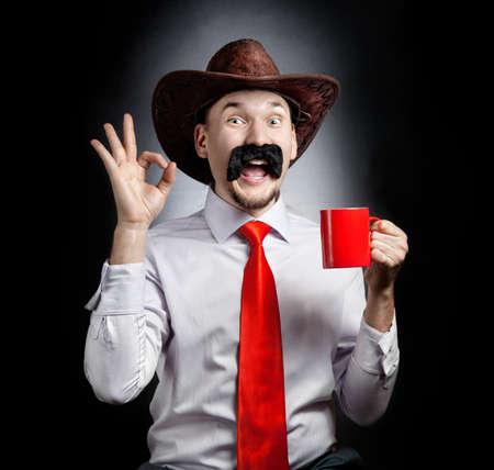 bigote: Vaquero divertido con el bigote grande que muestra gesto bien y que sostiene la taza roja en fondo negro