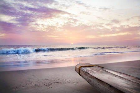 Part of boat on the beach near the ocean at sunset violet sky background in India Stock Photo
