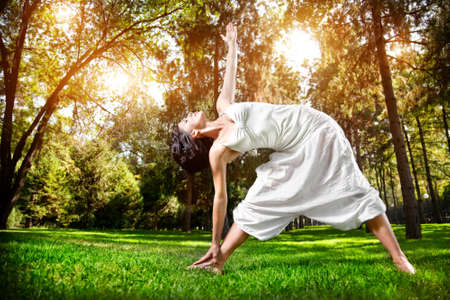 Yoga utthita trikonasana triangle pose by woman in white costume on green grass in the park around pine trees Stock Photo