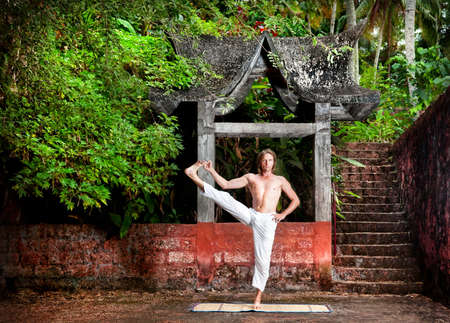 Yoga utthita hasta padangusthasana pose by man in white trousers near stone temple at sunset background in tropical forest  photo