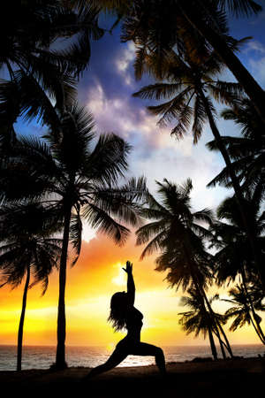 Woman silhouette doing virabhadrasana I warrior pose on the beach near palm trees at sunset background in India