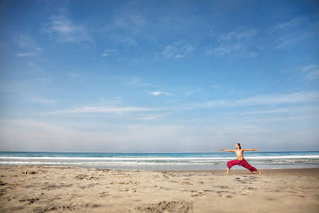 hatha: Yoga virabhadrasana II warrior pose by fit man with long hair in red trousers on the beach at ocean background  Stock Photo