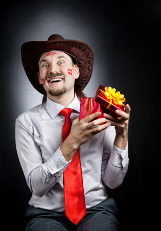 Happy cowboy with moustache and marks from red lipstick on his face holding red box present at black background photo