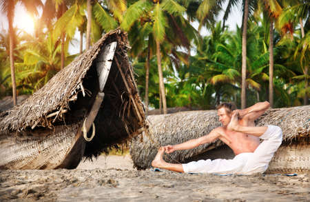 india fisherman: Yoga aakarna dhanurasana archer pose by fit man in white trousers on the beach near the fishermen boats in India Stock Photo